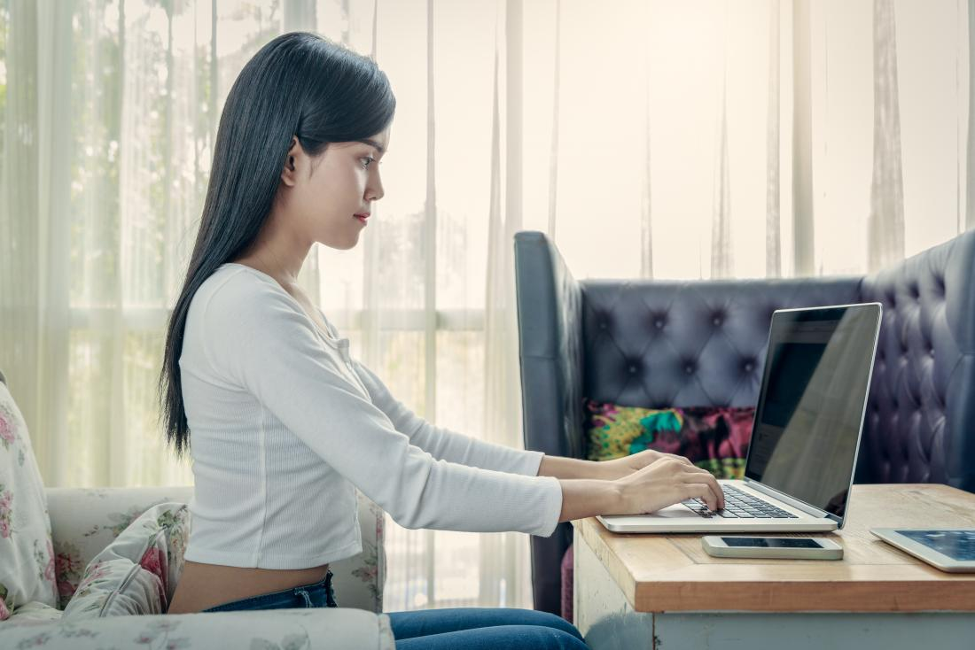 sitting-position-for-good-posture-with-woman-sitting-up-straight-typing-on-laptop বসে থেকেই ওজন কমান